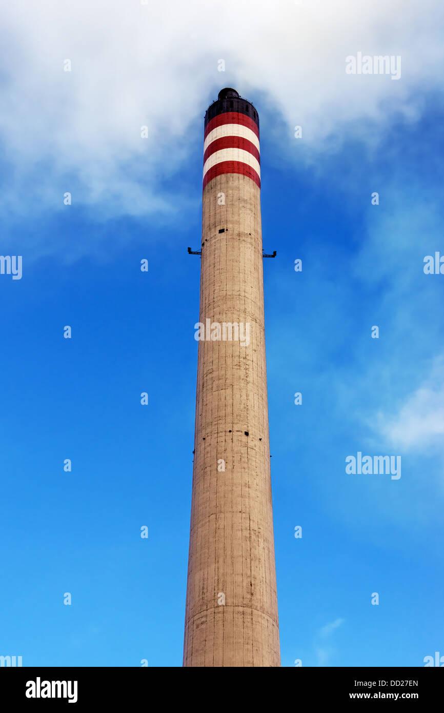 Raffinerie Schornstein erzeugt Rauch gegen blauen Himmel Stockbild