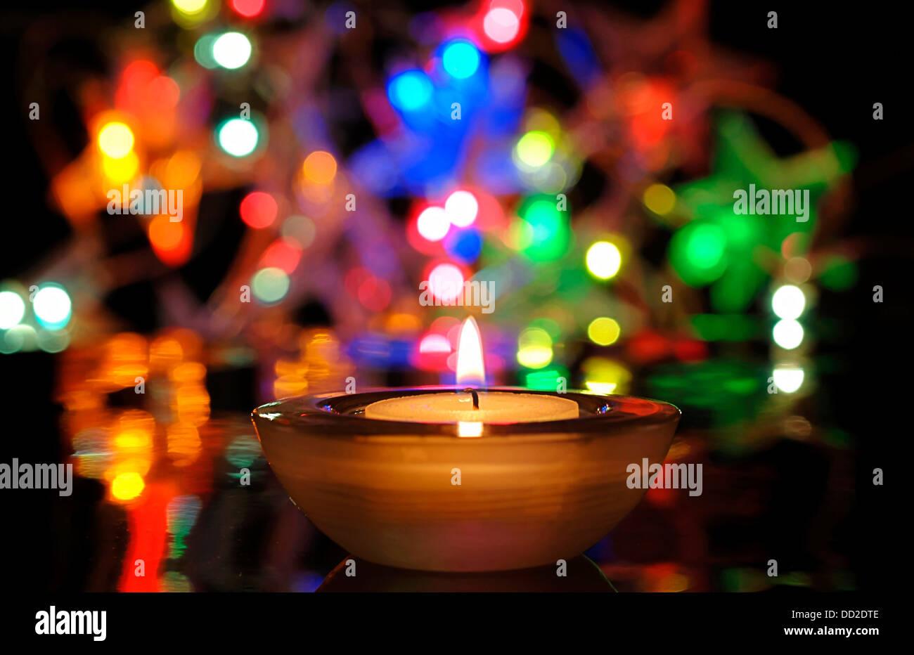 Weihnachtsbeleuchtung und brennende Kerze Stockbild