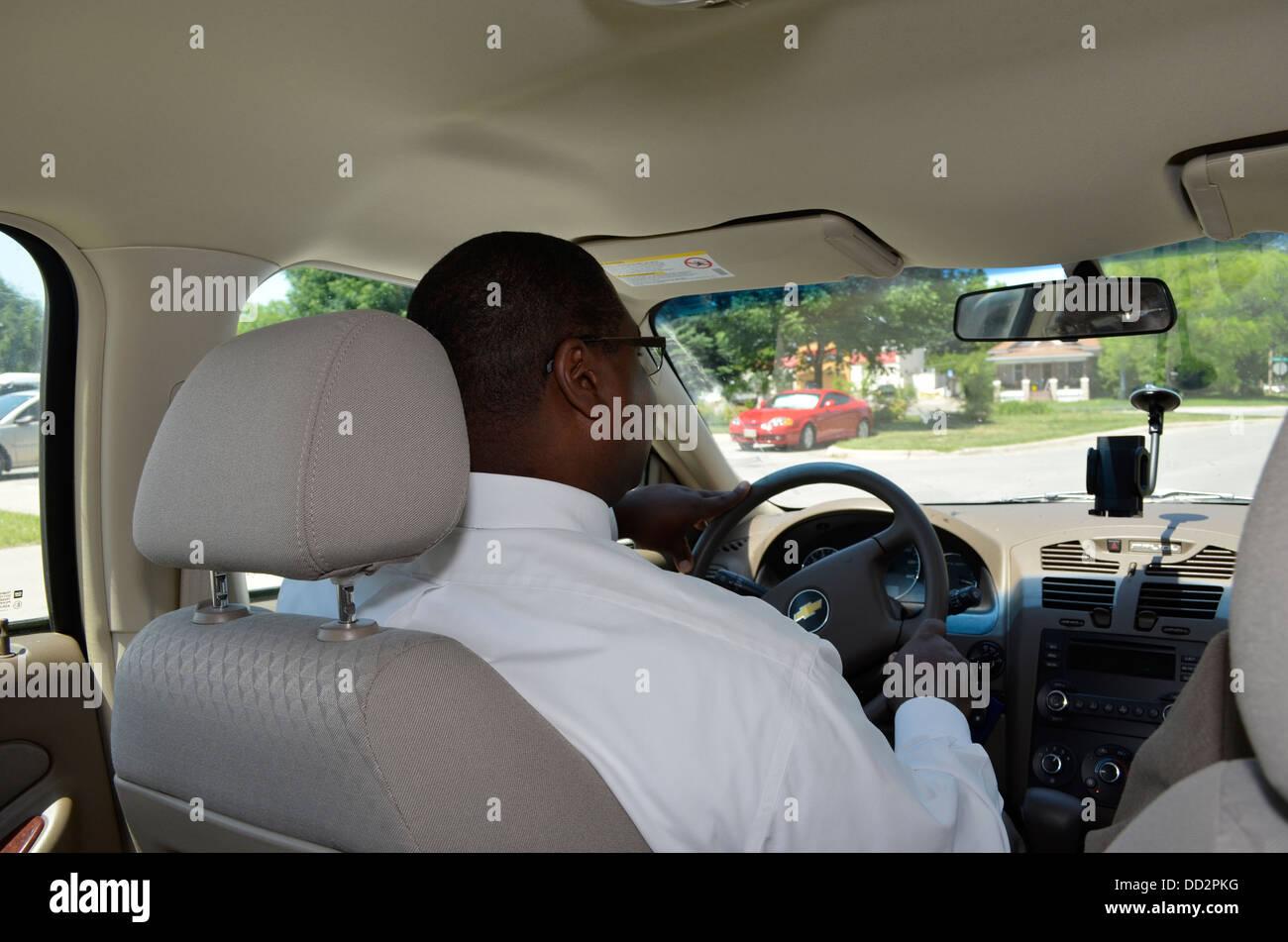 Zwei männliche Bewährungshelfer im Fahrzeug auf dem Weg zu einen Jugendstraftäter an seinem Arbeitsplatz Stockbild