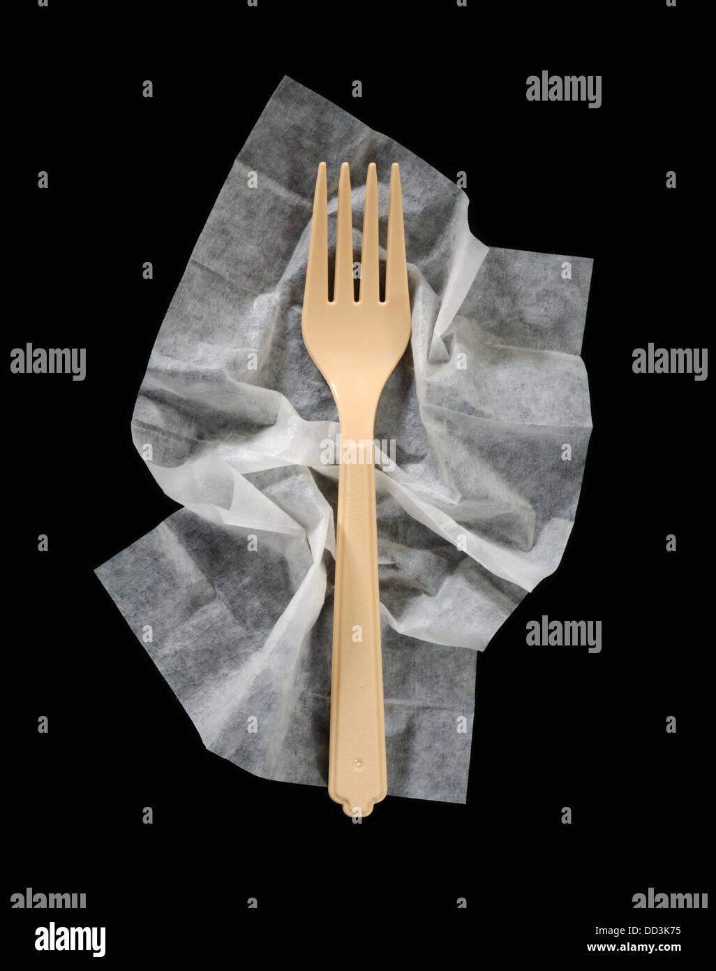 Ein Kunststoff Menuegabel auf einem zerknitterten Reinigung Serviette. Stockbild