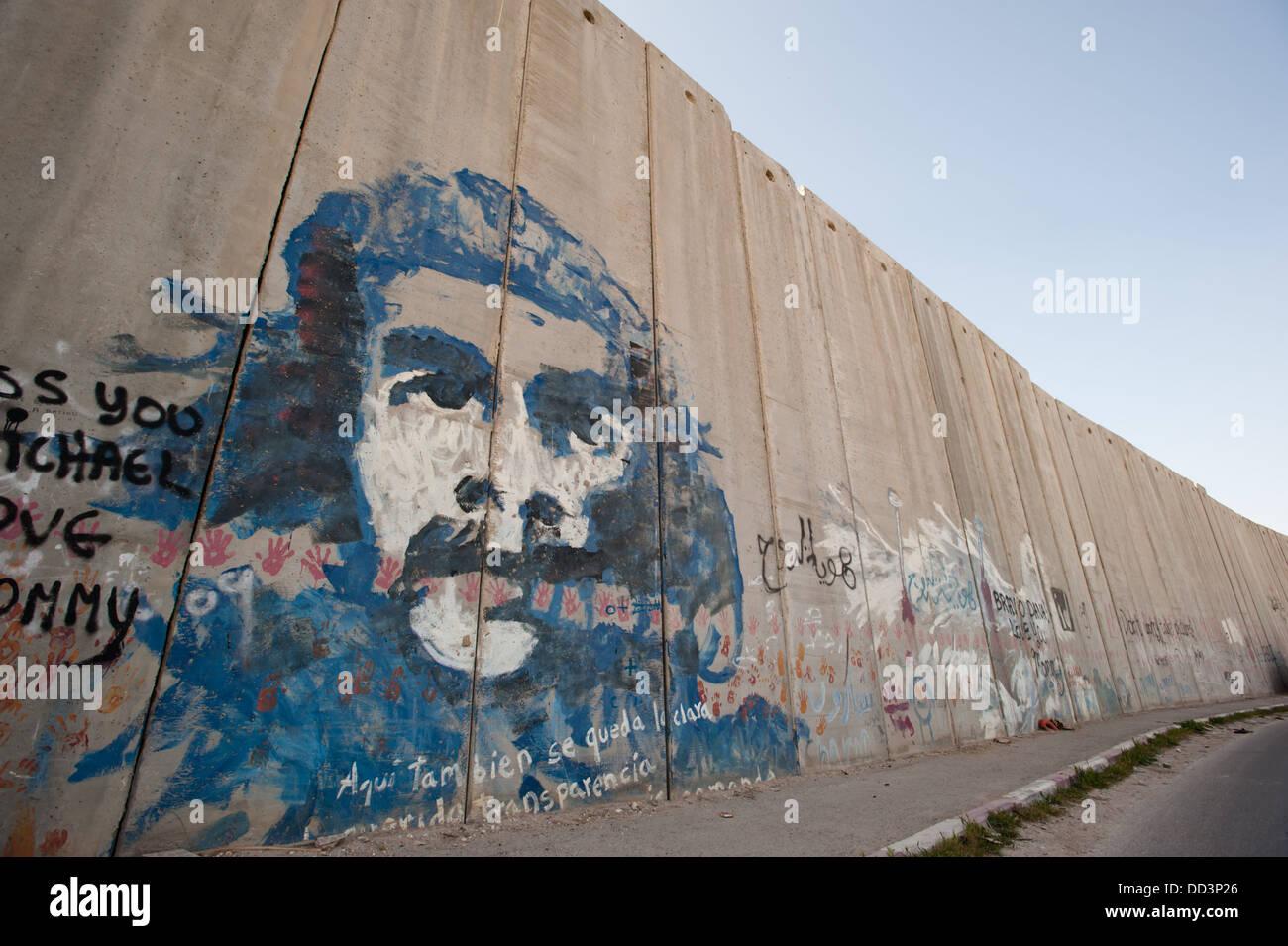 Ein Wandbild von Che Guevara deckt die israelischen Trennmauer in der palästinensischen Stadt Abu Dis. Stockbild