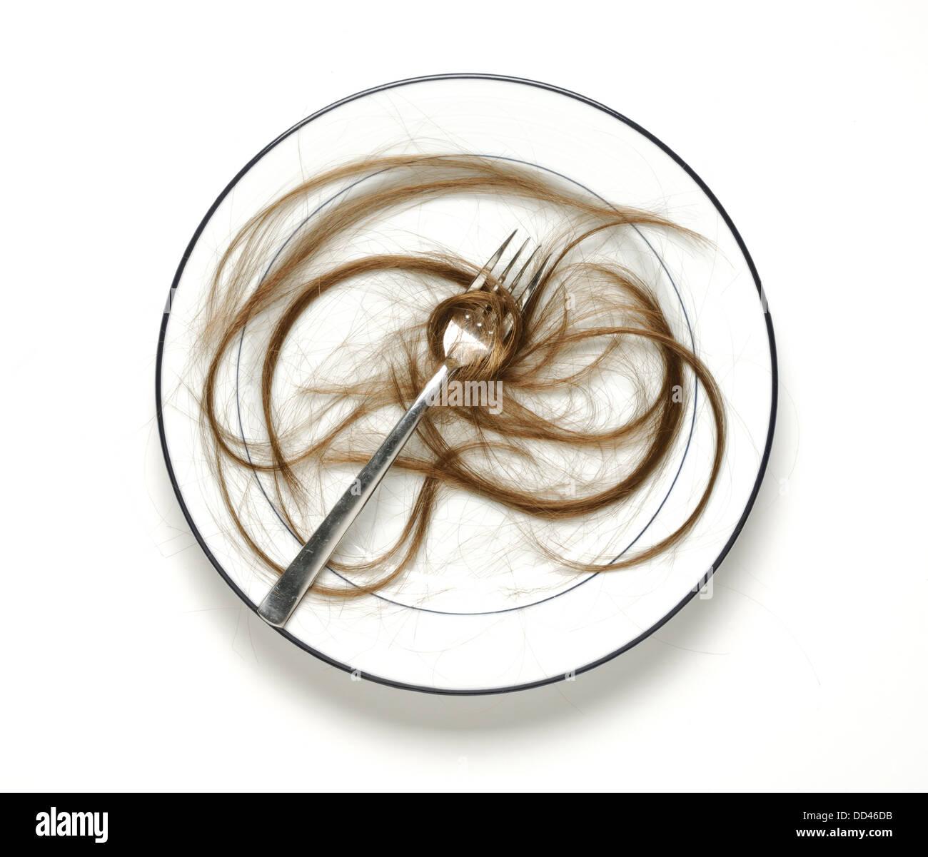 Ein Wohn / Teller mit einer Gabel und viele Bereiche des menschlichen Haares Stockbild