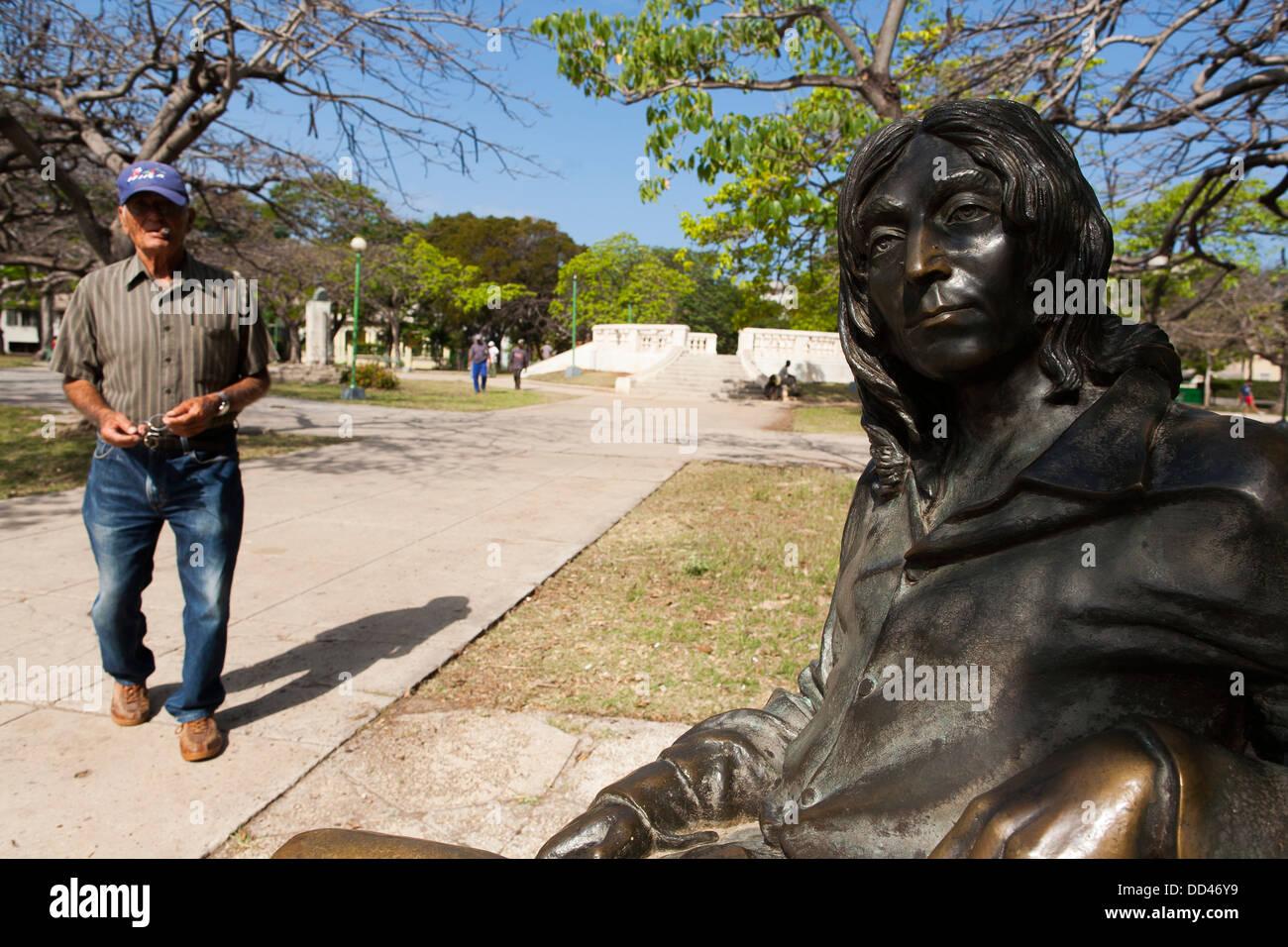 Eine Statue von John Lennon sitzen auf einer Bank ohne Brille im ...