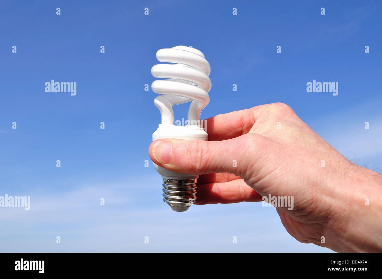 Hand, die eine energiesparende Glühbirne Stockbild