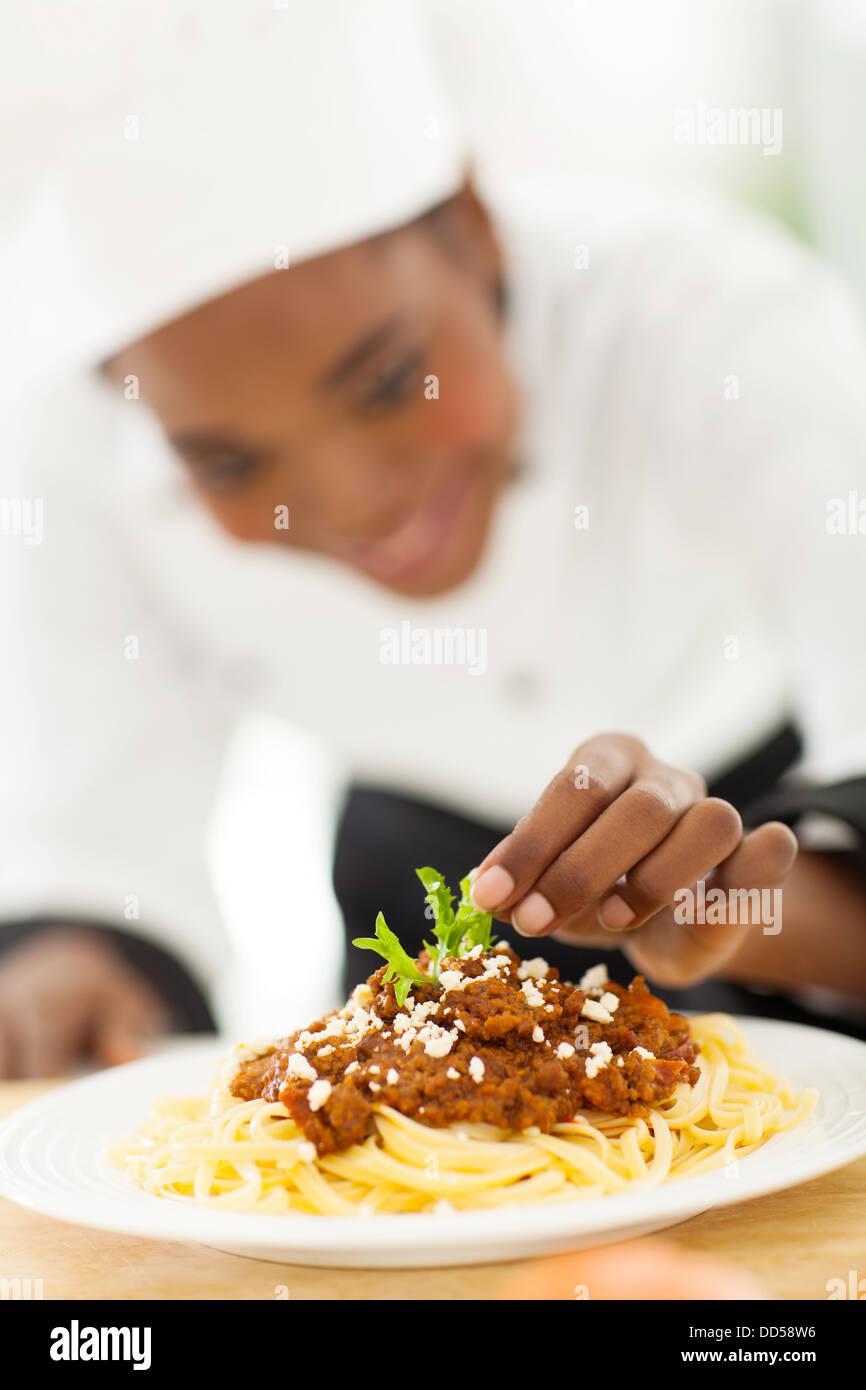 Afrikanische Köchin Garnierung Spaghetti in modernen Küche Stockbild
