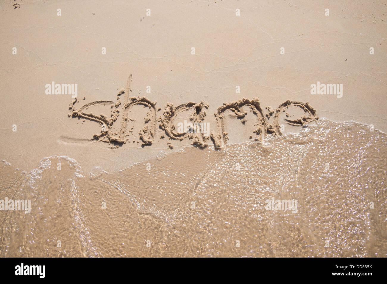 """Das Wort """"Schande"""", geschrieben in den Sand, die von einer Welle weggespült. Stockbild"""