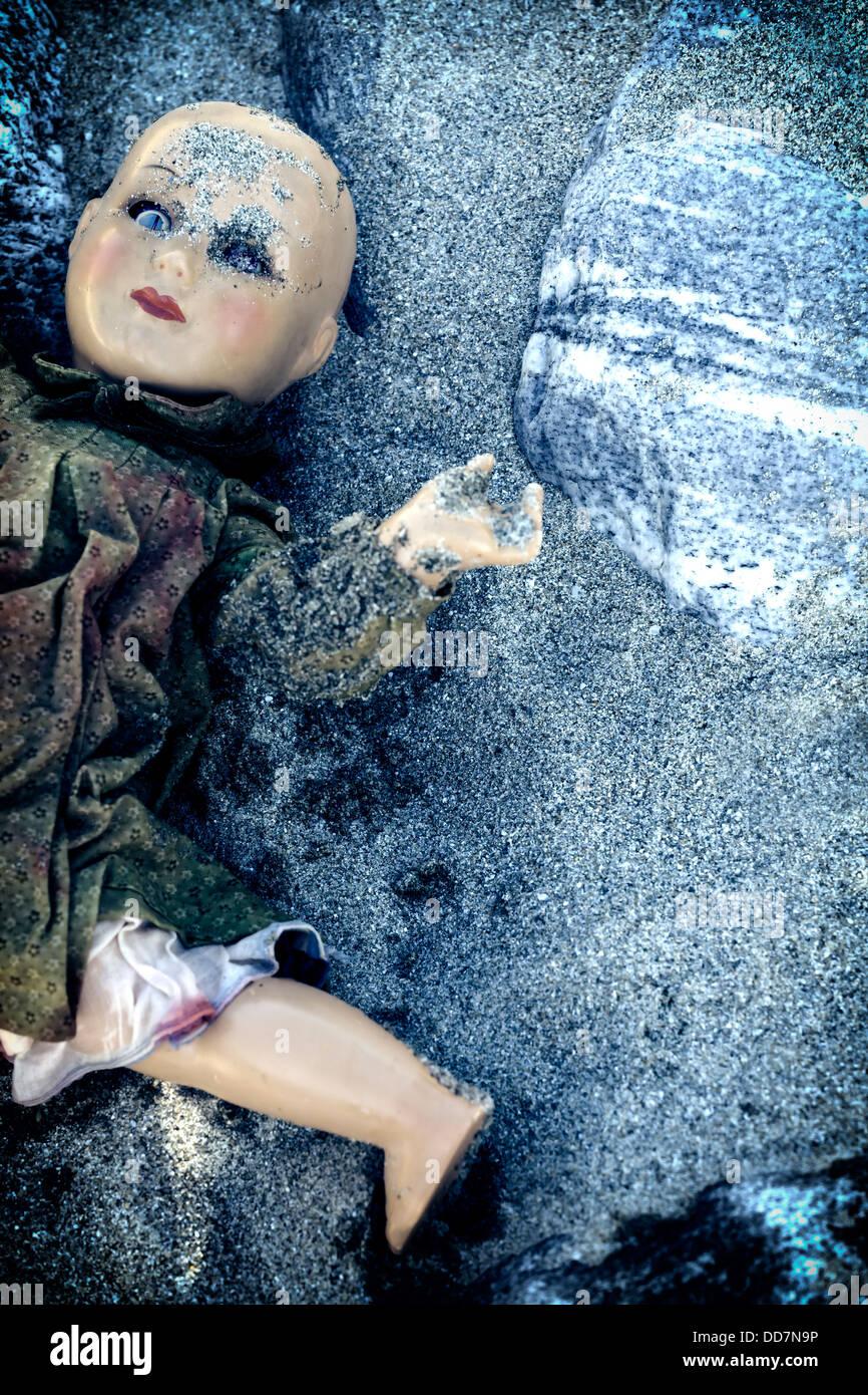 eine kaputte Puppe, halb im Sand begraben Stockbild