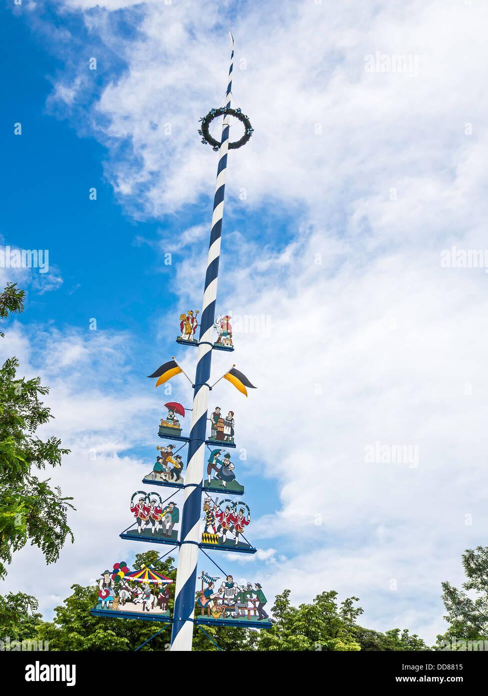 Bild von einer typischen traditionellen bayerischen Maibaum mit blauem Himmel und weißen Wolken Stockbild