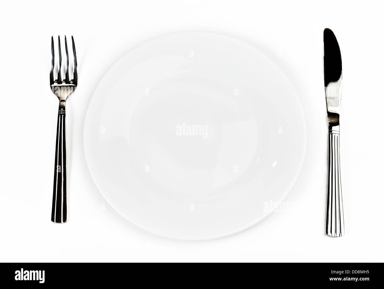 Teller mit Besteck: Messer und Gabel, über weiß Stockbild