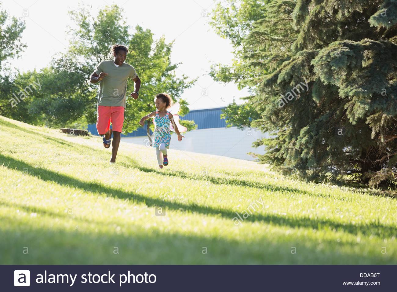 Fröhliche Vater und Tochter im Park laufen Stockbild