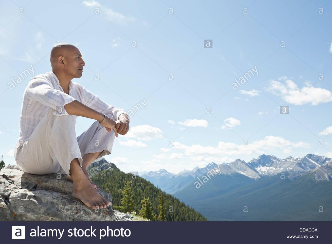 Reifer Mann sitzen auf Berggipfel Stockbild