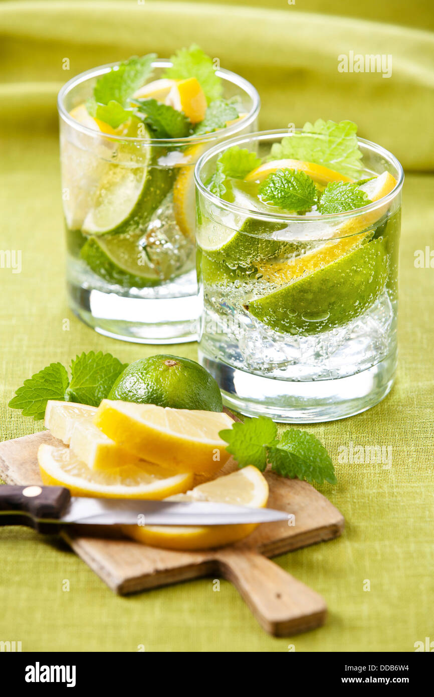 Kalte frische Limonade mit Zitrone und Limette auf grünem Hintergrund Stockbild
