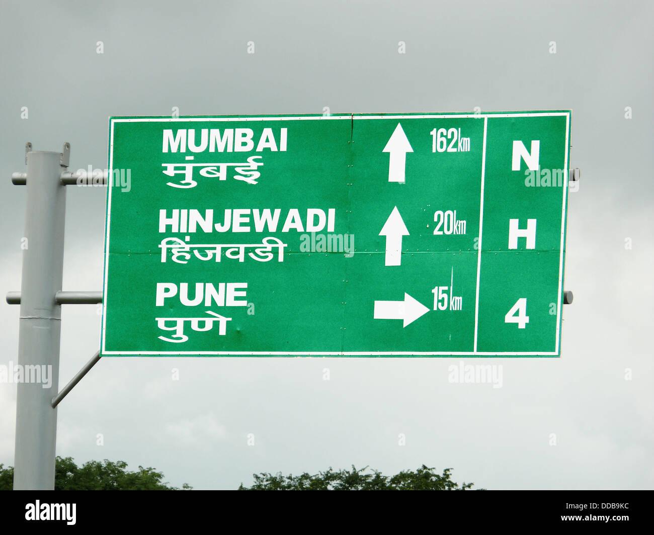 Eine symbolische Board auf einer Bundesstraße am Straßenrand zeigt Entfernungen von bestimmten Orten aus Stockbild