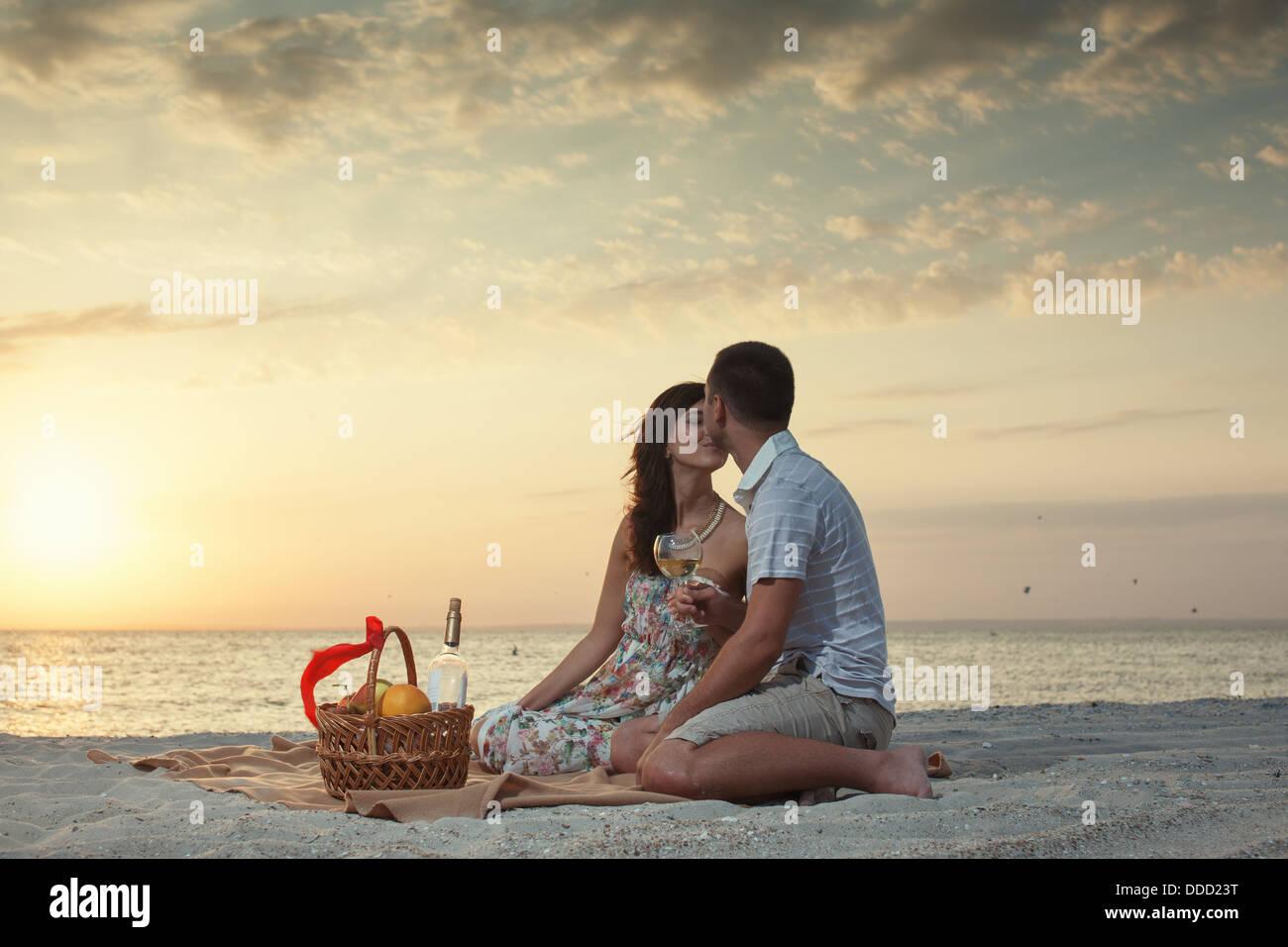 Paar am Strand mit Luxus Wein Picknick bei Sonnenuntergang. Dawn Stockbild