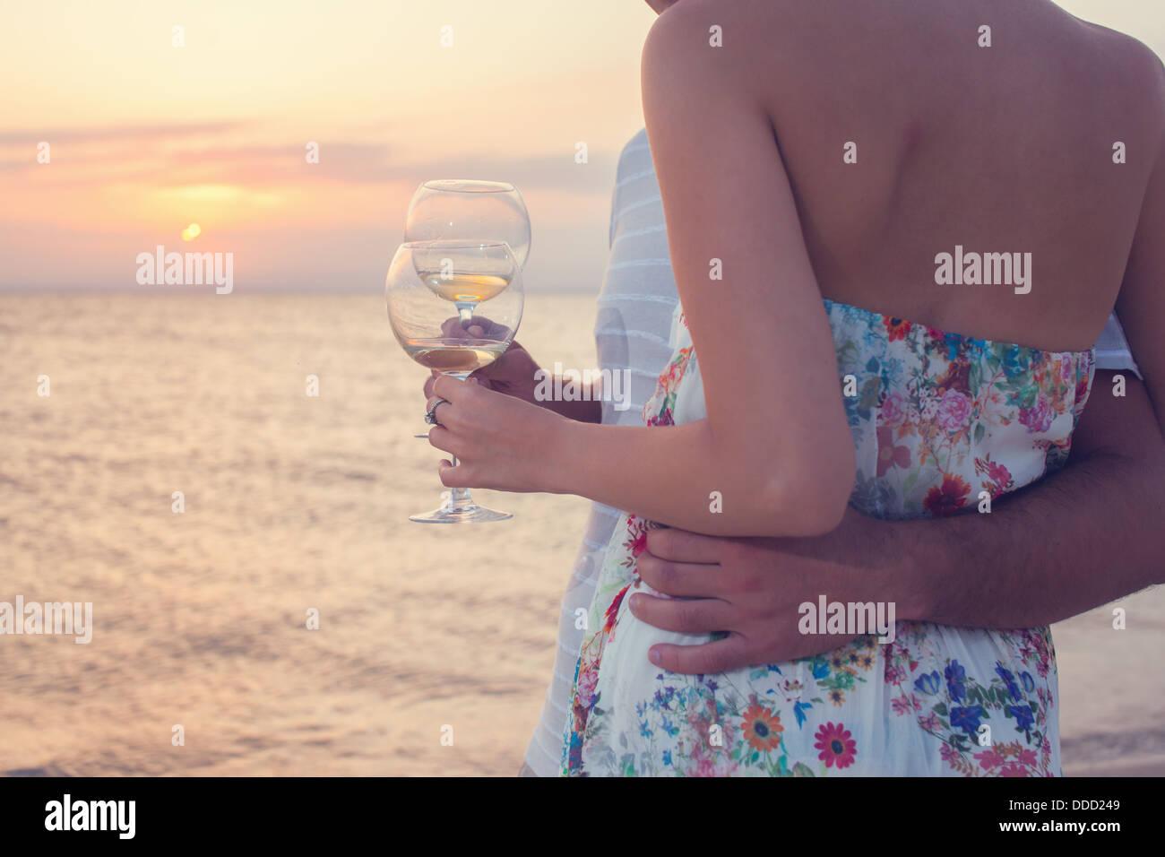 Nahaufnahme von Gläsern mit Weißwein bei Sonnenuntergang am Strand. Paar auf Picknick. Stockbild