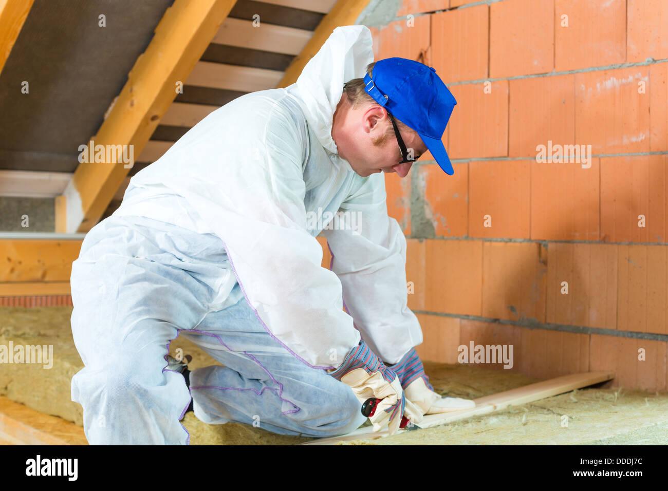 Arbeitnehmer insgesamt ist isolierendes Material mit Handschuhen und Messer schneiden. Stockbild