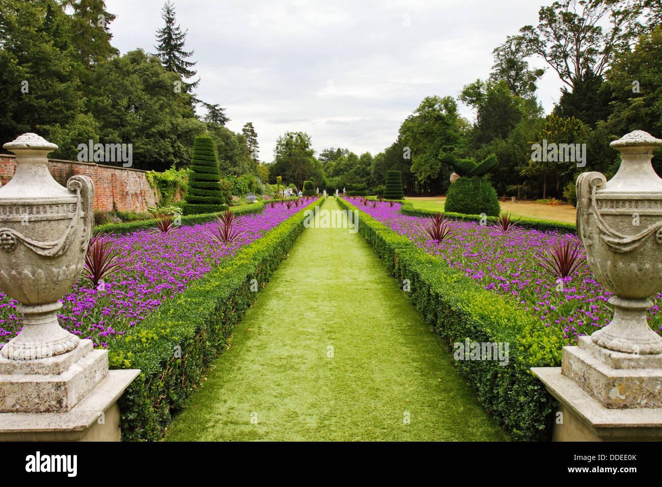 Ein formaler englischer Landschaftsgarten mit Box Hedging und Statuen auf Sockeln Stockbild