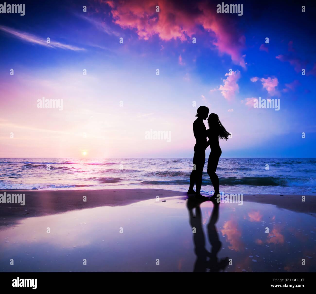 Romantisches Paar küssen am Strand bei Sonnenuntergang Stockfoto