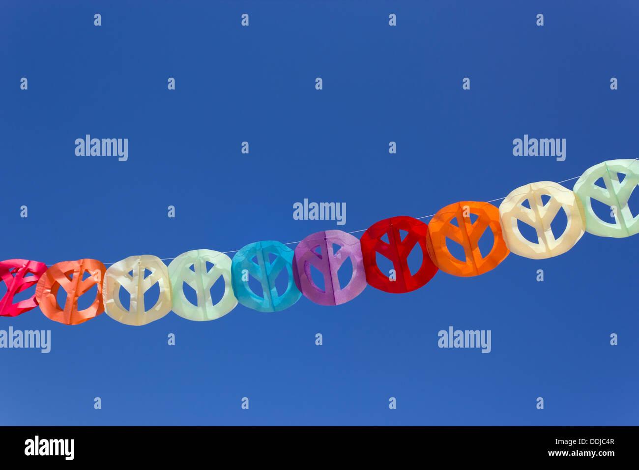 Papier Girlande aus bunten Peace-Zeichen gegen blauen Himmel. Stockbild