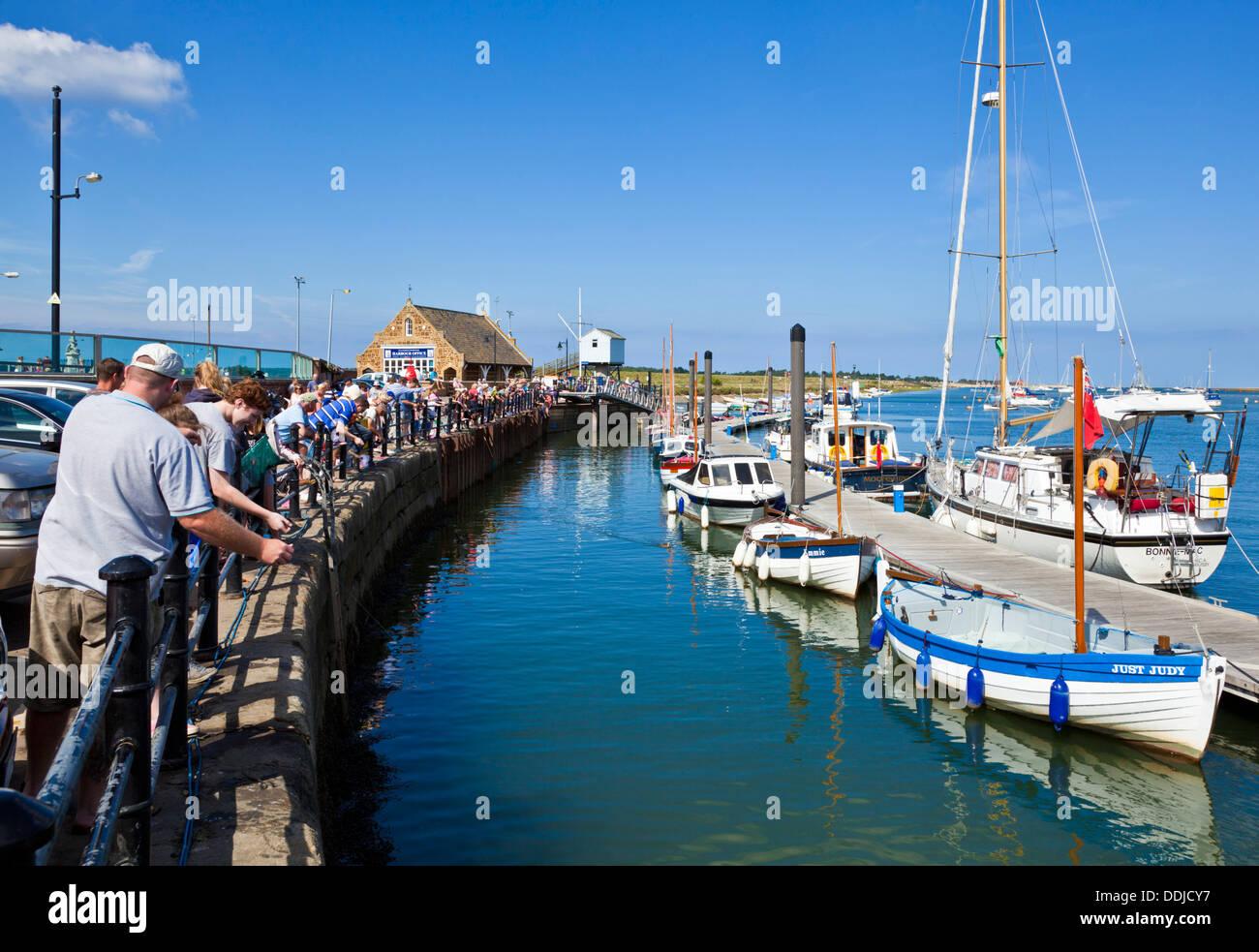 Urlaubern für Krebse angeln oder Verdrehungen im Hafen von Brunnen neben das Meer North Norfolk Küste England UK Stockfoto