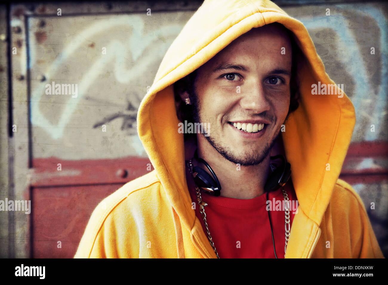 Teenager / junge Mann Porträt in Sweatshirt mit Kapuze / Jumper auf Grunge-Graffiti-Wand Stockbild