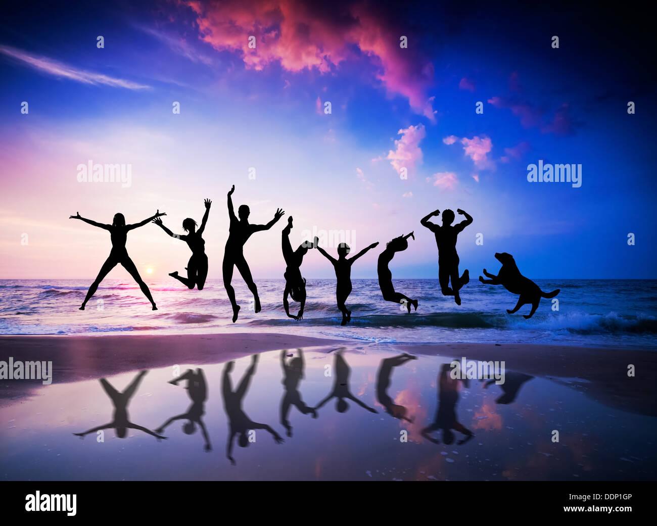 Glückliche Menschen und Hund springen zusammen am Sonnenuntergang Strand Stockbild