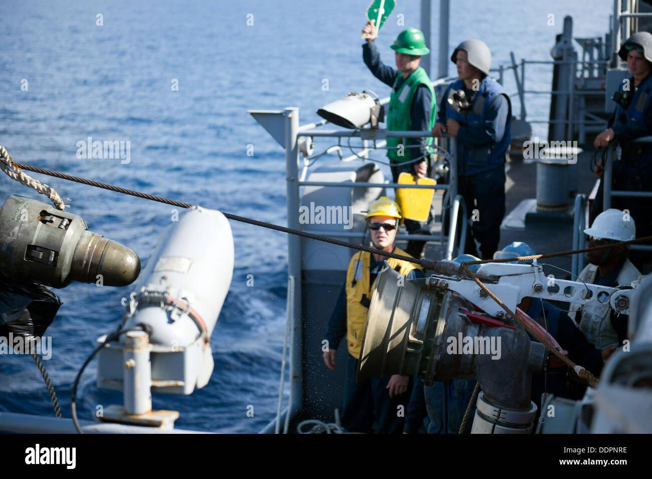 Eine Betankung Düse löst von einem Empfänger an Bord Dock amphibischen Transportschiff USS Denver (LPD 9) während einer laufenden Nachschub (UNREP) mit amphibischer Angriff Schiff USS Bonhomme Richard (LHD-6). Denver ist auf Streife mit der Bonhomme Richard Amphib Stockbild