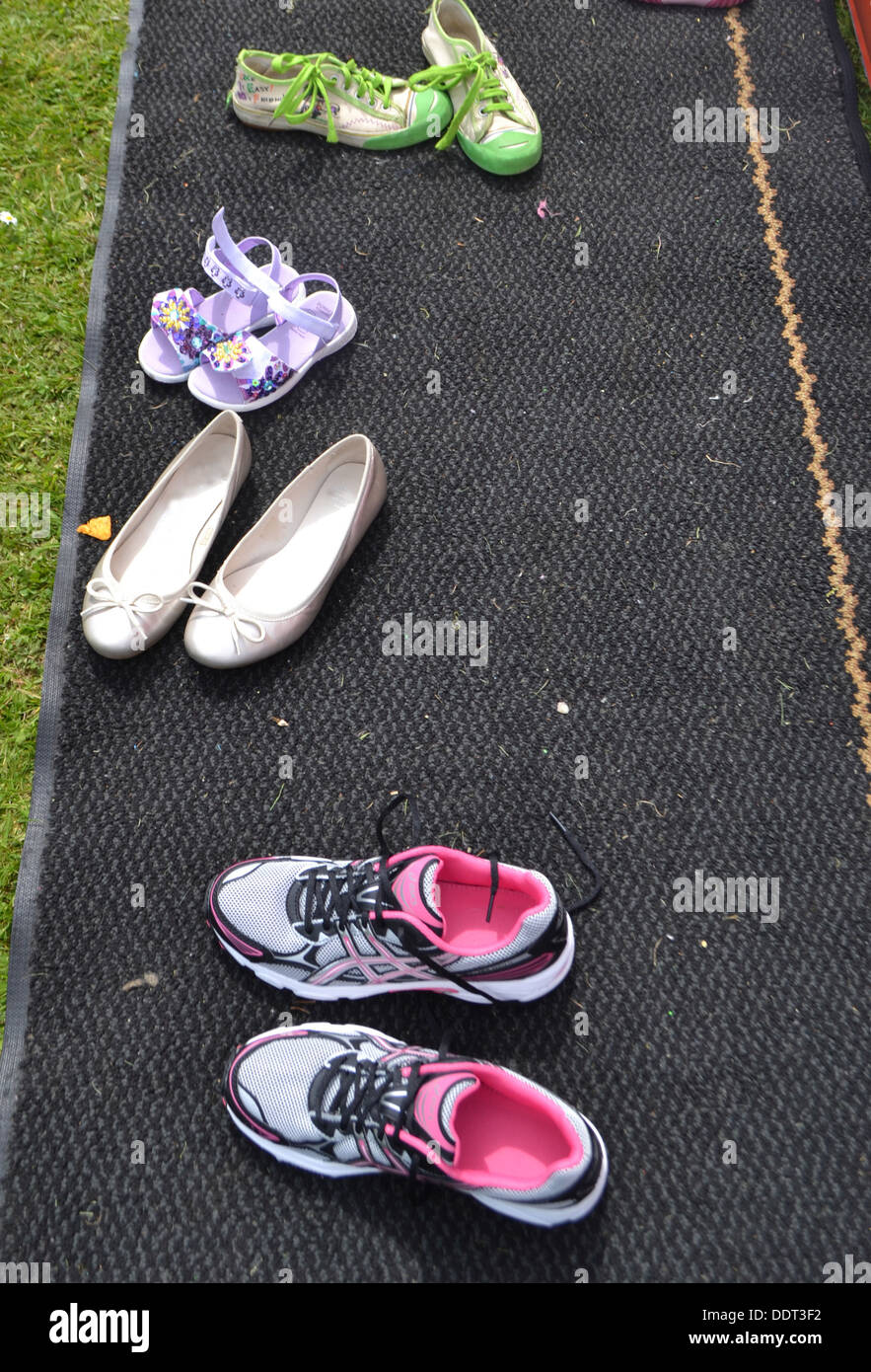 Kinderschuhe auf einer Matte neben einer Hüpfburg Stockbild