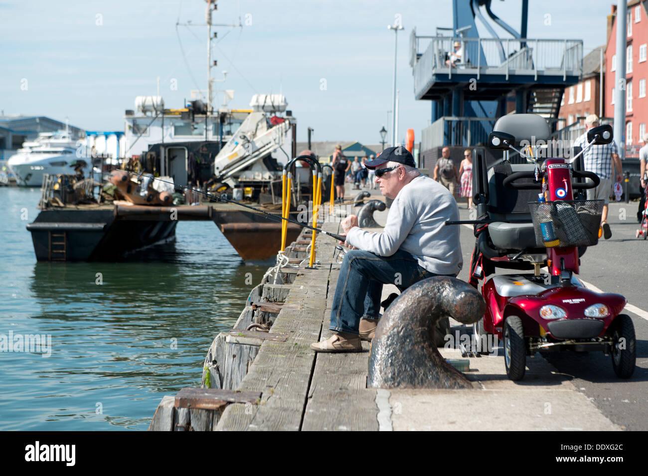 Ein Rentner sitzt Angeln am Kai in Poole in der Grafschaft Dorset in Südengland. Stockbild