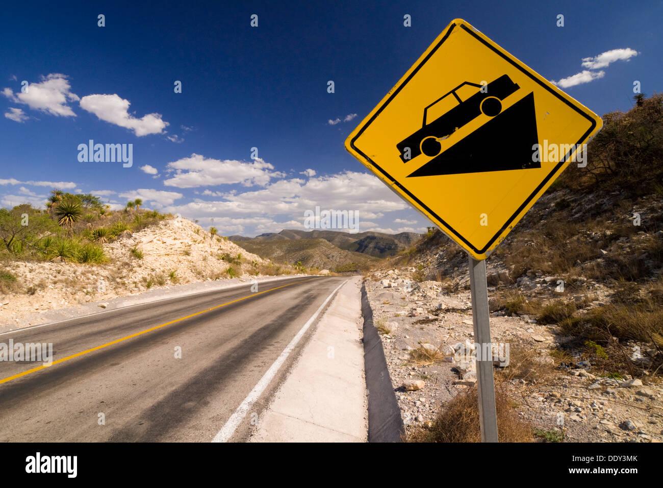 Warnzeichen auf einer abschüssigen Straße Stockbild