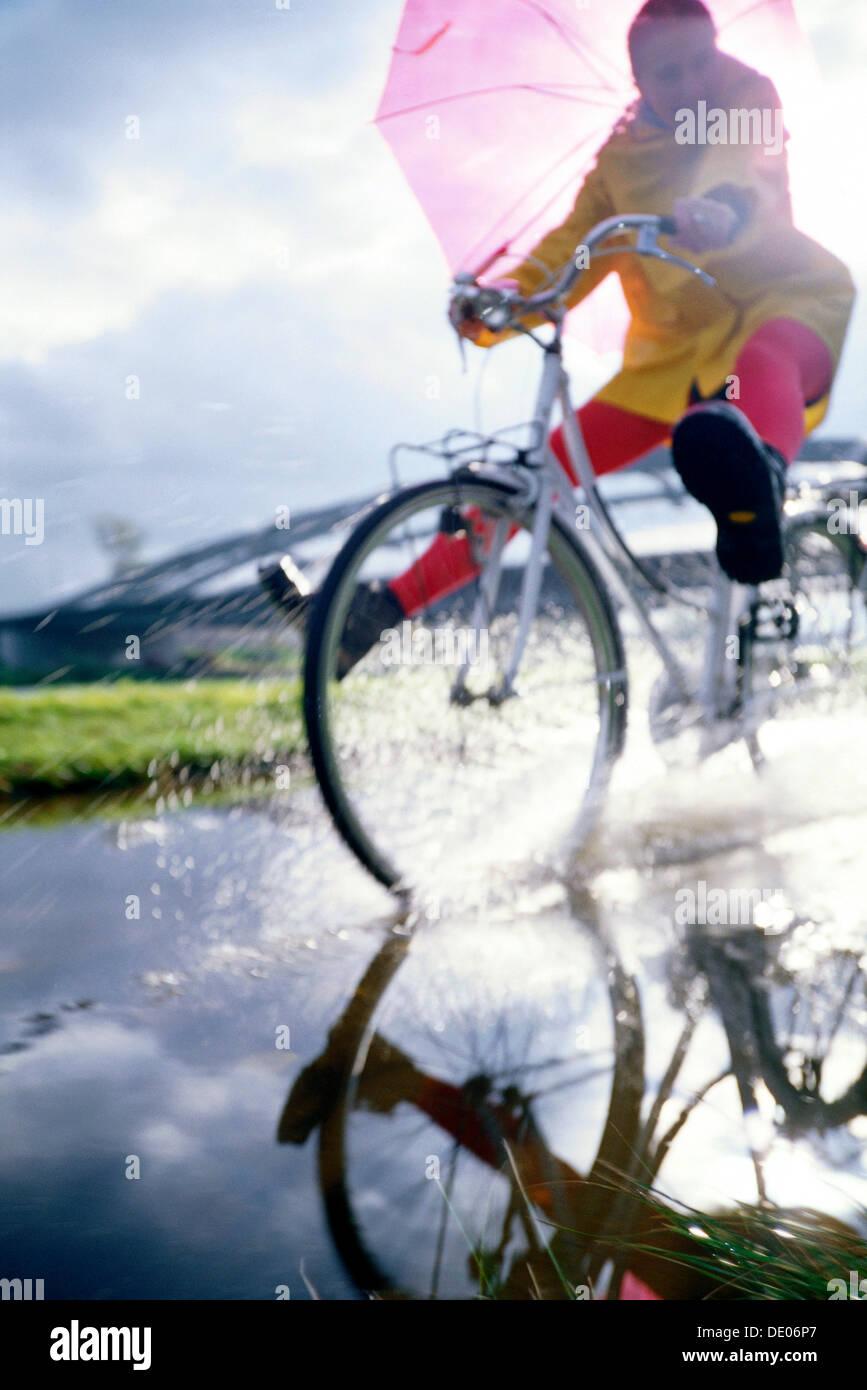 Radfahrer mit einem Regenmantel und einen Regenschirm, Reiten durch eine Wasserpfütze Stockbild
