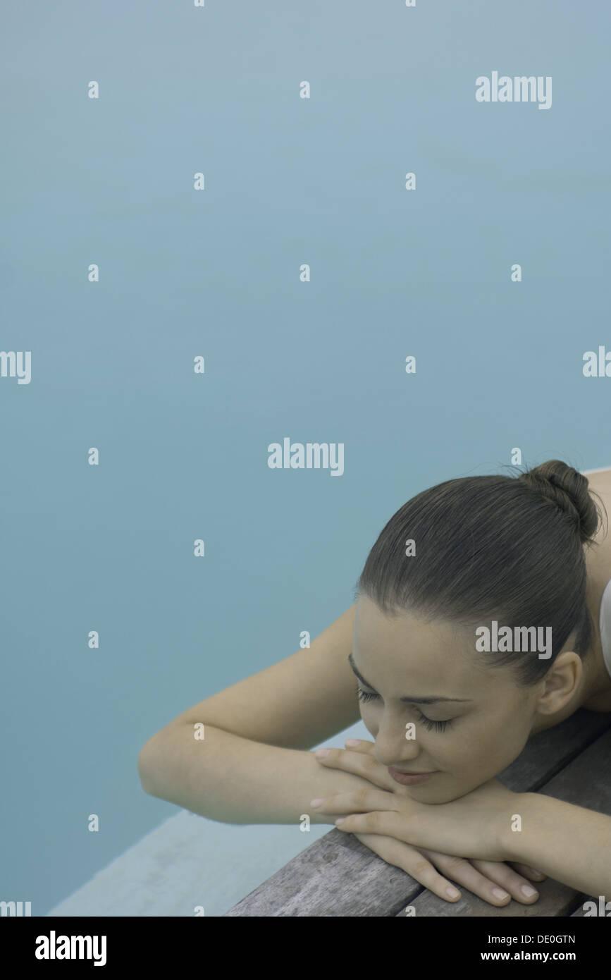 Frau liegend neben Pool, Kopf auf Arme, geschlossenen Augen ruhen Stockbild