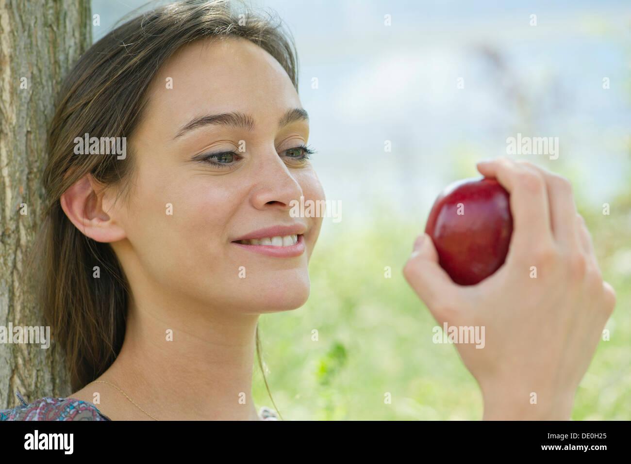 Frau sitzt im Freien mit Apfel Stockbild