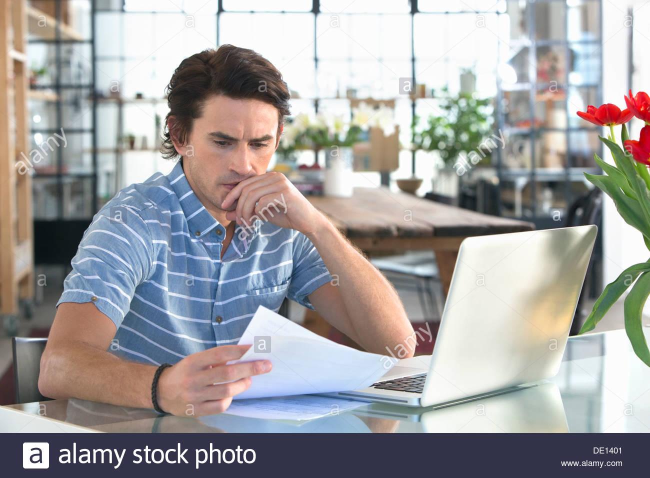 Ernster Mann mit Laptop blickte auf Papierkram am Küchentisch Stockbild