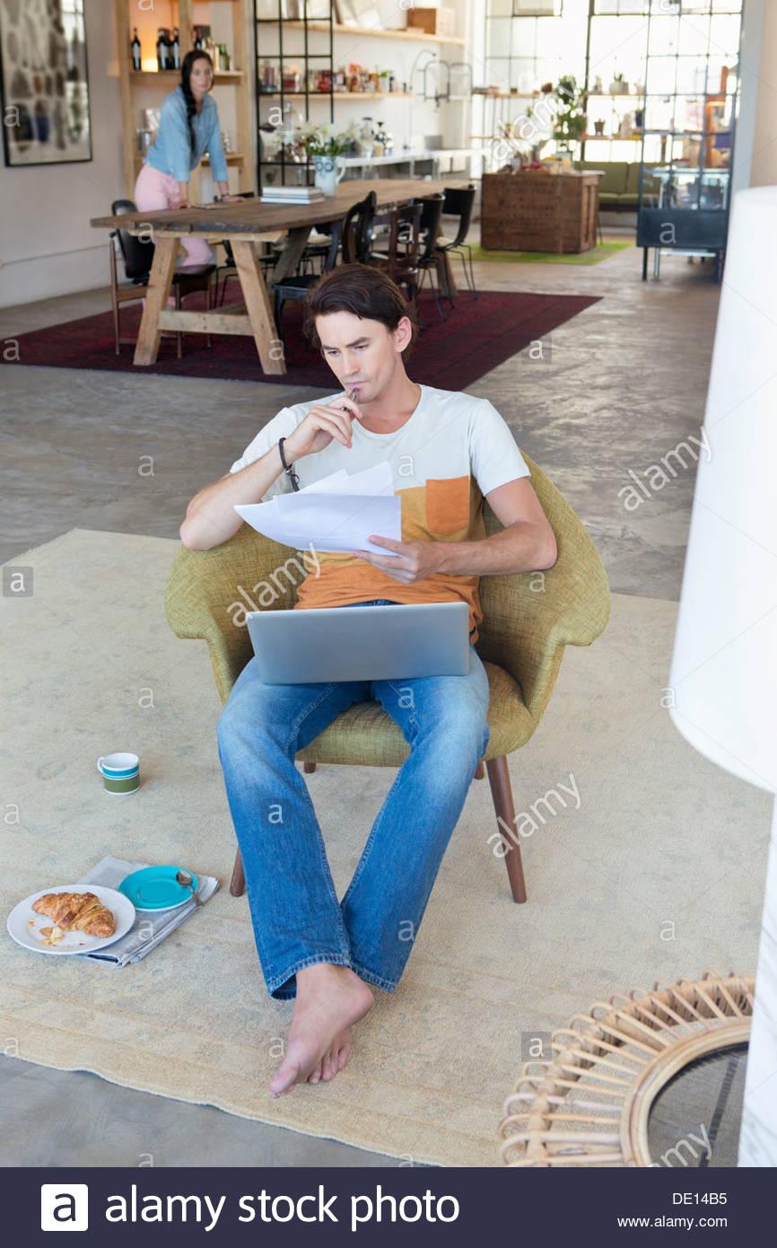 Ernster Mann blickte auf Papierkram und Laptop im Wohnzimmer Stockbild