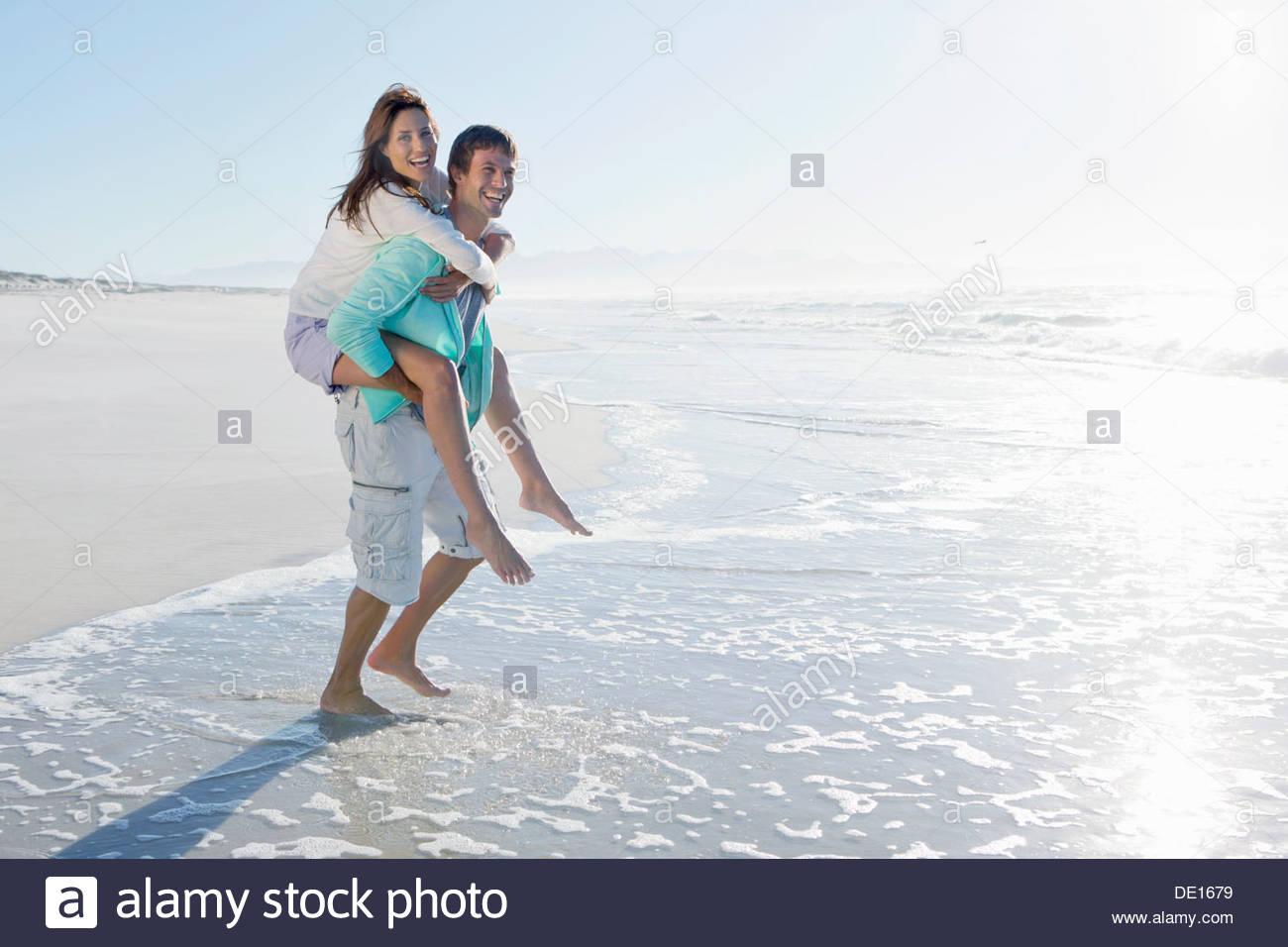 Mann, die Frau in der Brandung am sonnigen Strand Huckepack Stockbild