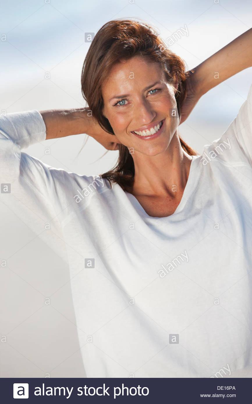 Porträt der lächelnde Frau mit Händen hinter dem Kopf am Strand Stockbild