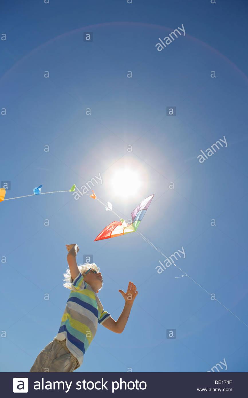 Junge, springen und für Kite unter Sonne am blauen Himmel erreichen Stockbild