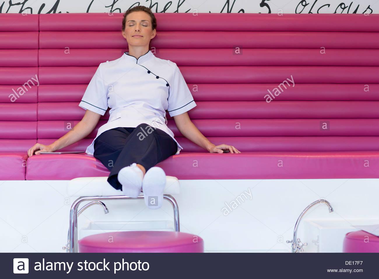 Kosmetikerin mit geschlossenen Augen auf die Sitzbank im Salon entspannen Stockbild