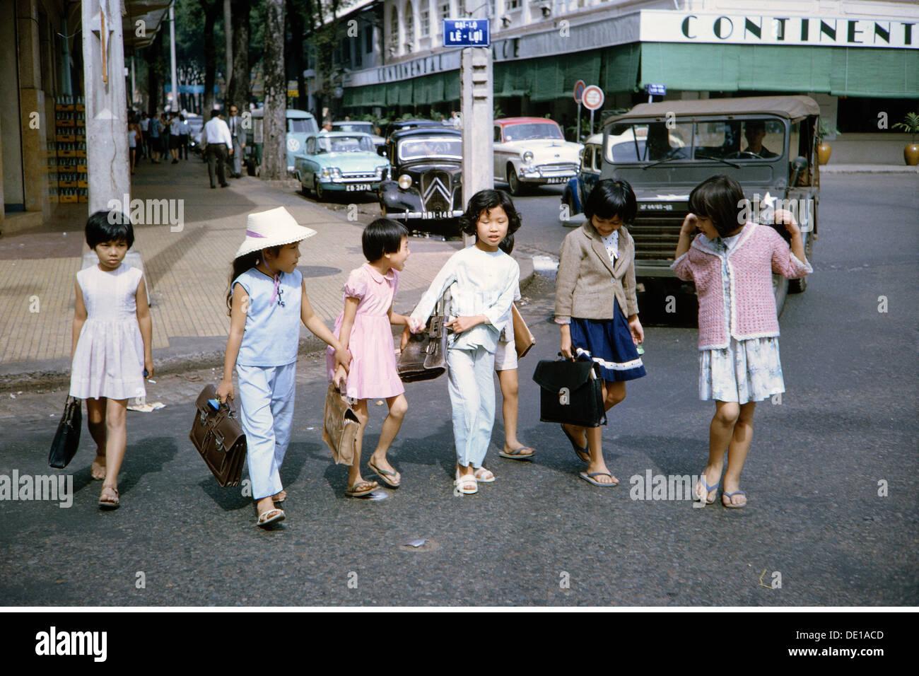 Vietnam Krieg 1957 - 1975,Vietnamesische Schulkinder auf der Straße in der Nähe des Hotels Continental,Saigon,Südvietnam,1965,Zivilbevölkerung,Zivilisten,Schüler,Schüler,Schüler,Studenten,Schulmädchen,Schülerinnen,Militär,Streitkräfte,Jeep,Jeeps,Militär,Nam Stockfoto