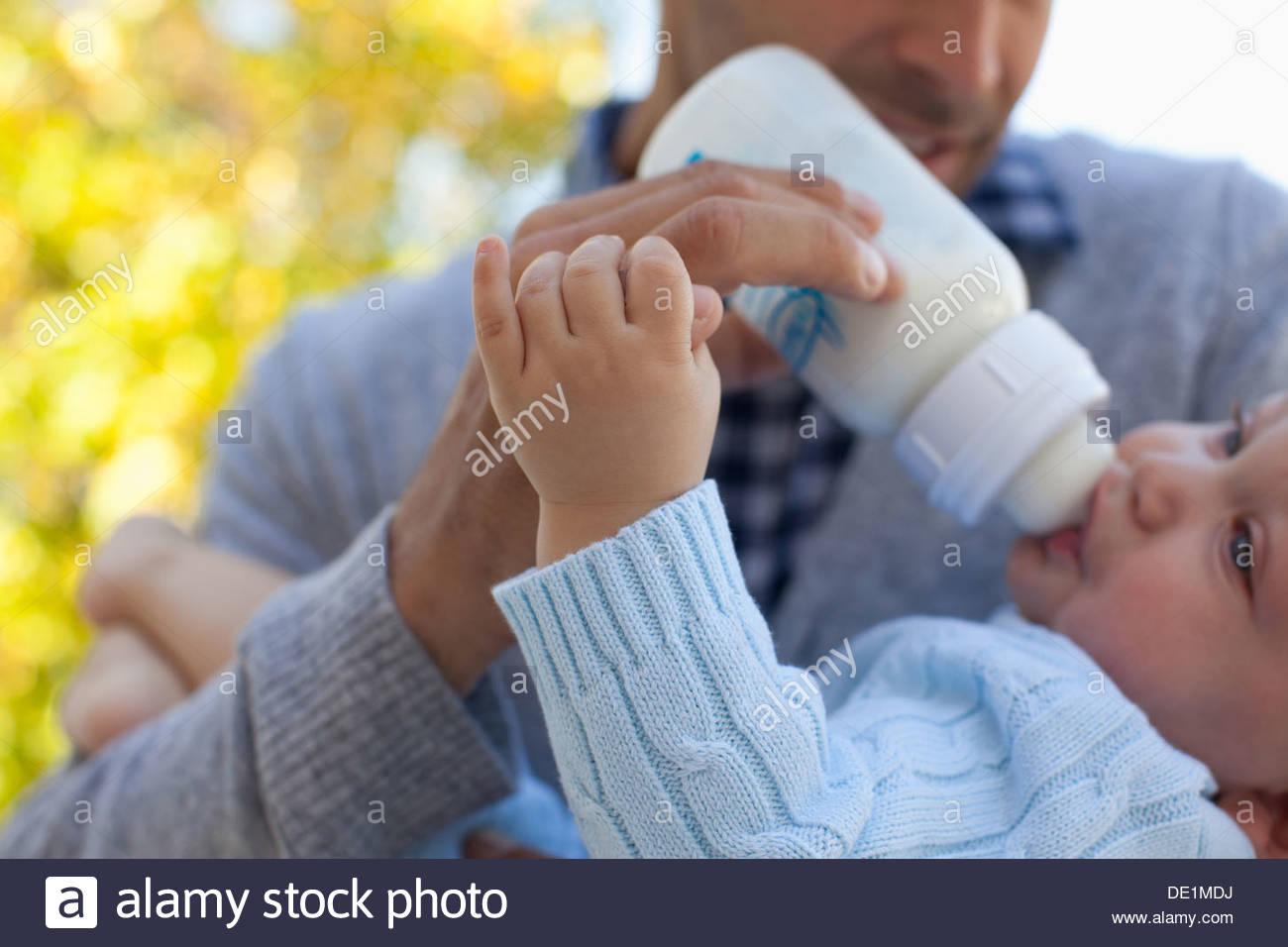 Vater Fütterung Baby aus der Flasche Stockbild