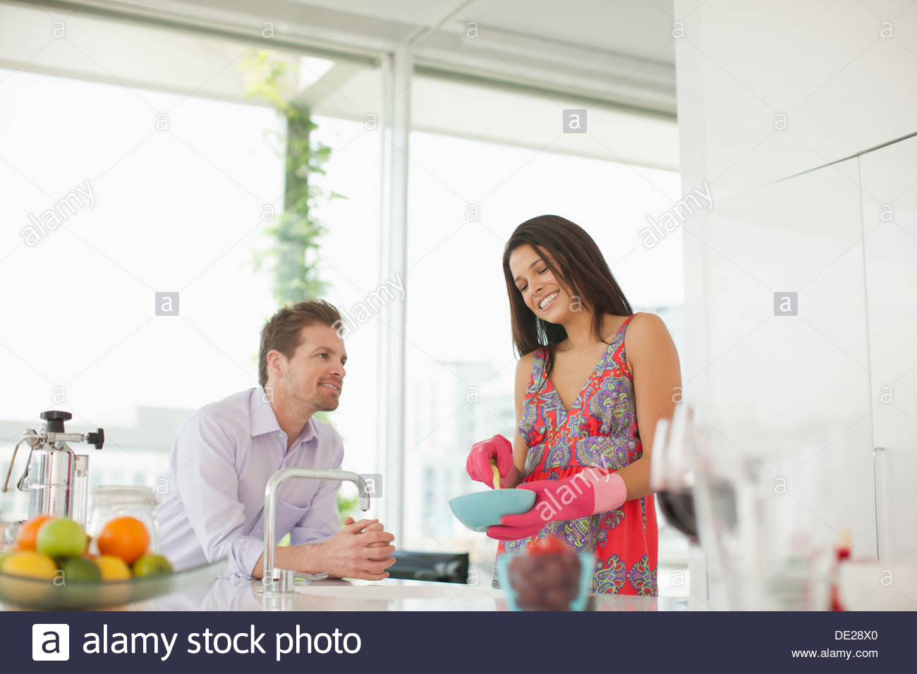 Mann beobachtet Frau Geschirrspülen Stockbild