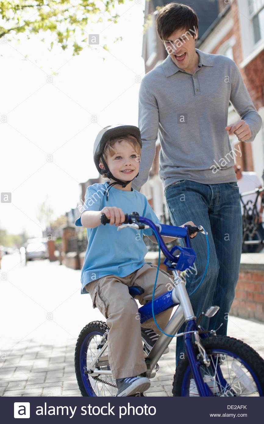Vater Sohn Fahrt Fahrrad auf Bürgersteig beobachtete Stockbild