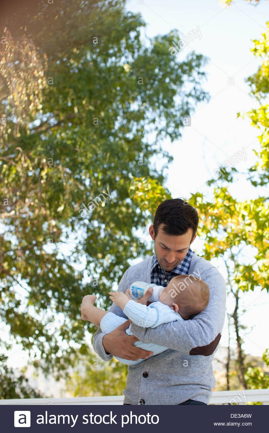 Vater mit der Flasche füttern Baby im freien Stockbild
