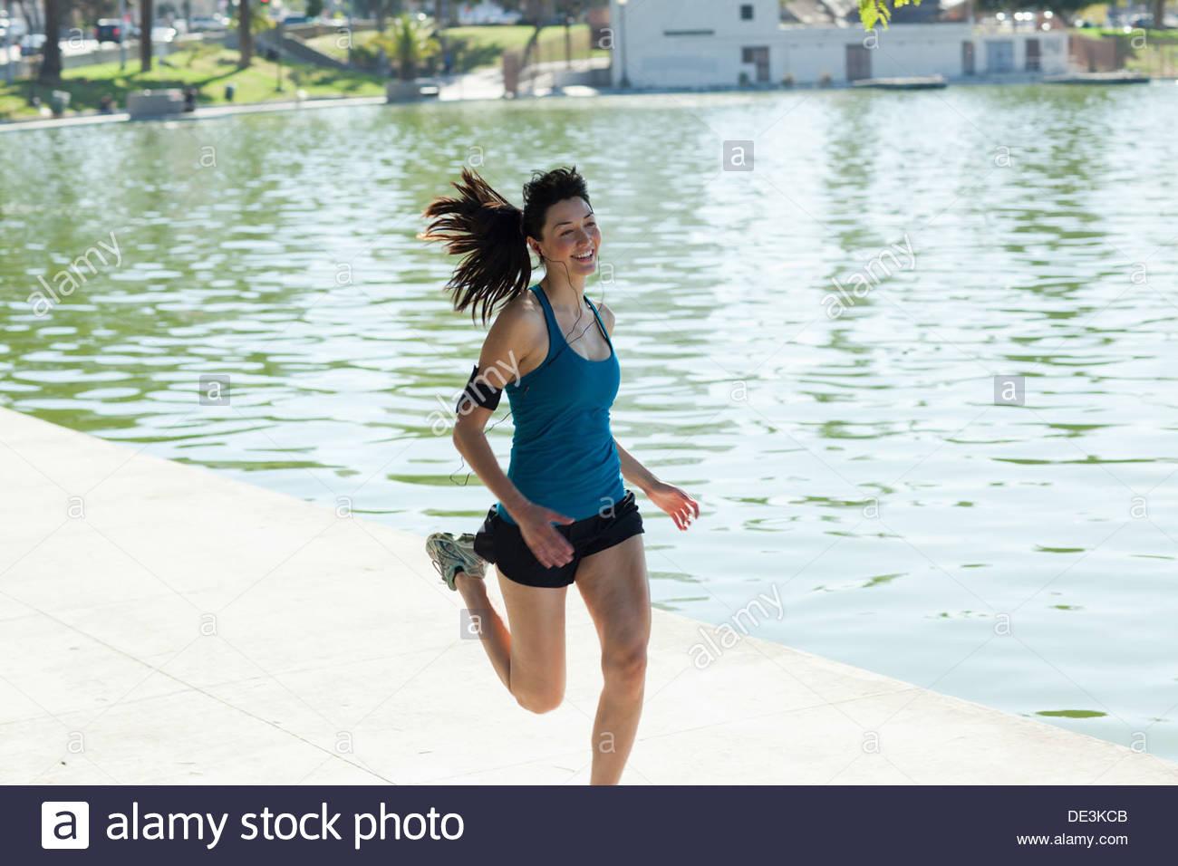 Frau läuft entlang See Stockbild