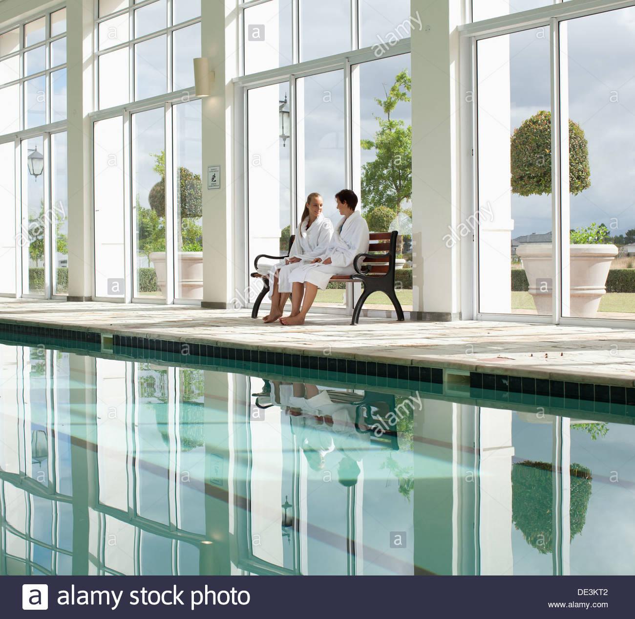 Zwei Frauen sitzen neben Schwimmbad Stockbild