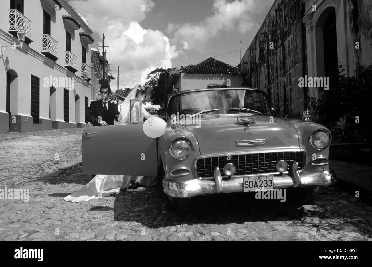 Cuban Hochzeitspaar erhöht in roten Chevrolet Stockbild