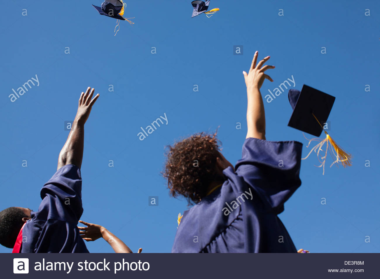 Absolventinnen und Absolventen werfen Kappen in Luft im freien Stockbild