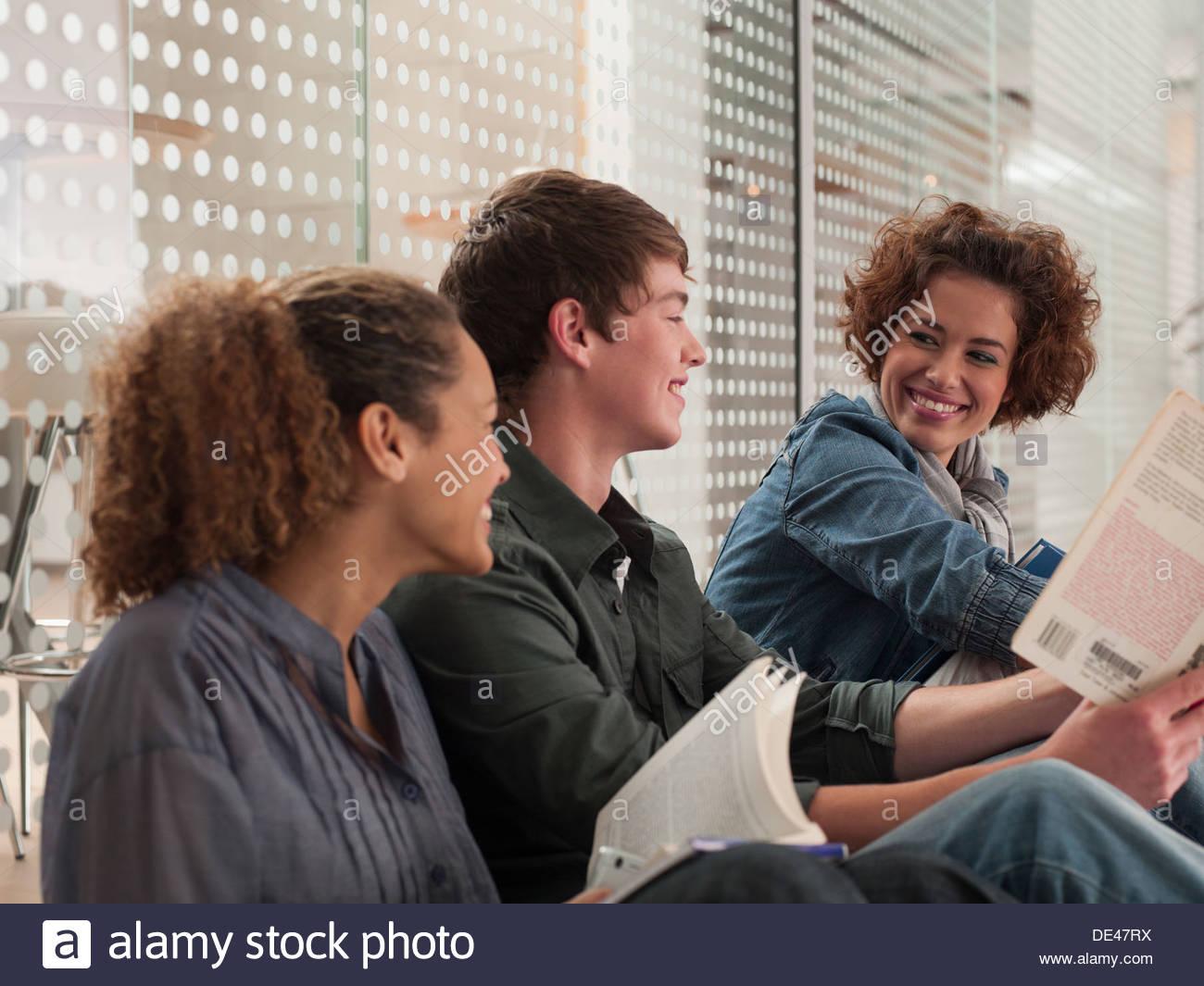 Lächelnden Freunde sitzen in einer Reihe mit Buch Stockbild