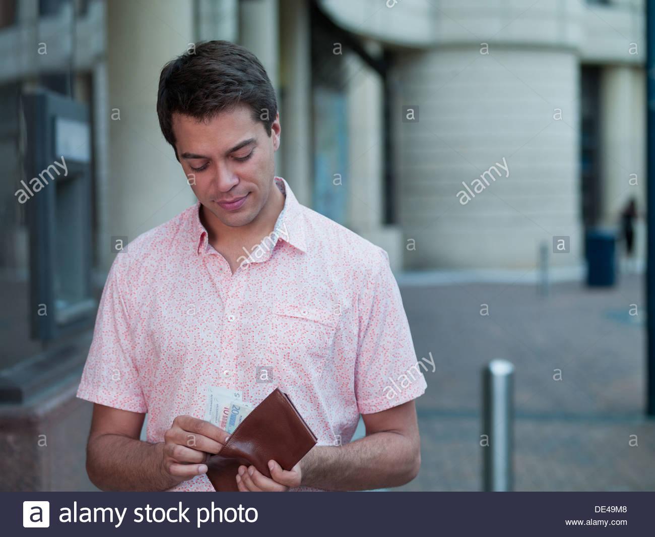 Mann, hält die Tasche in der Nähe von Geldautomaten Stockbild